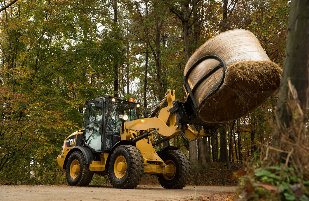 Cat M Series Ag Handler compact wheel loader with hay bale
